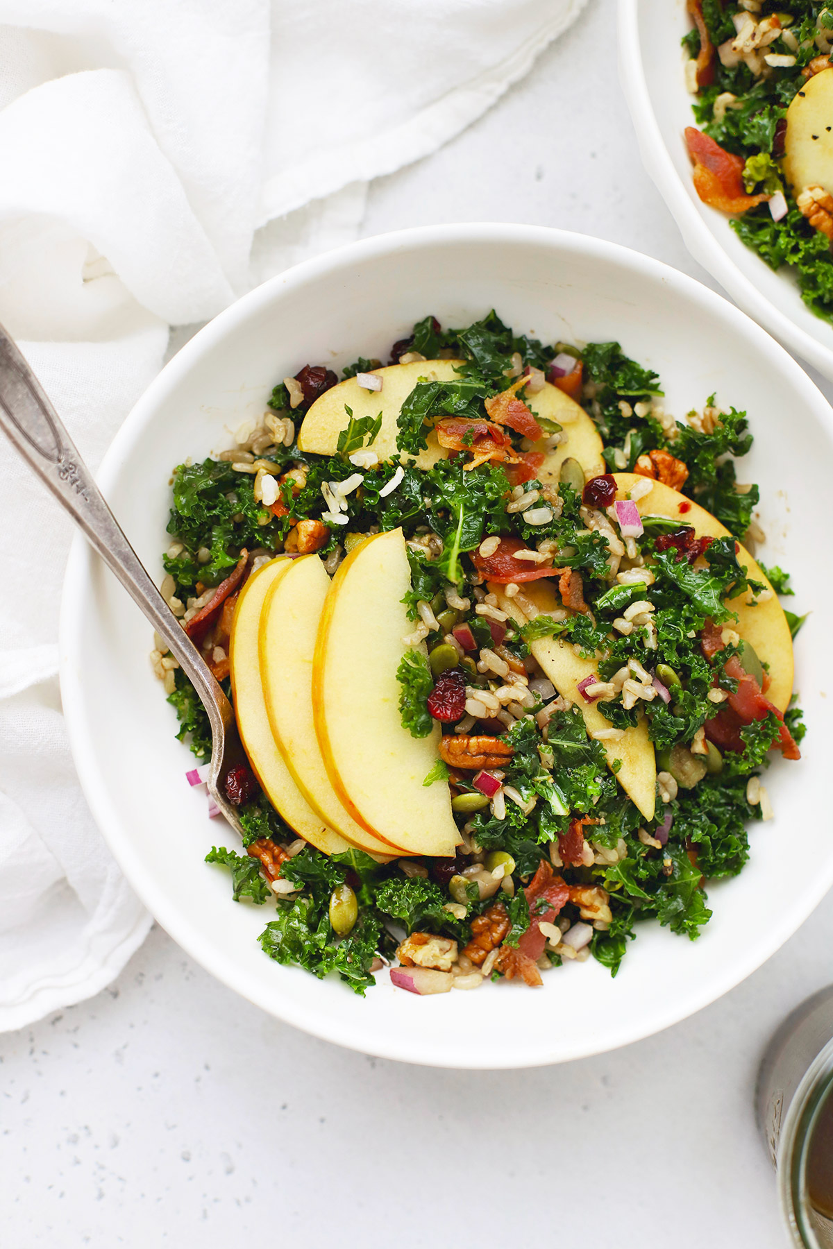 White bowl of Harvest Apple Kale Salad with Balsamic Dressing