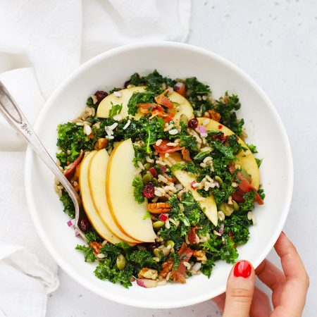 Setting down a bowl of Harvest Apple Kale Salad on a white background