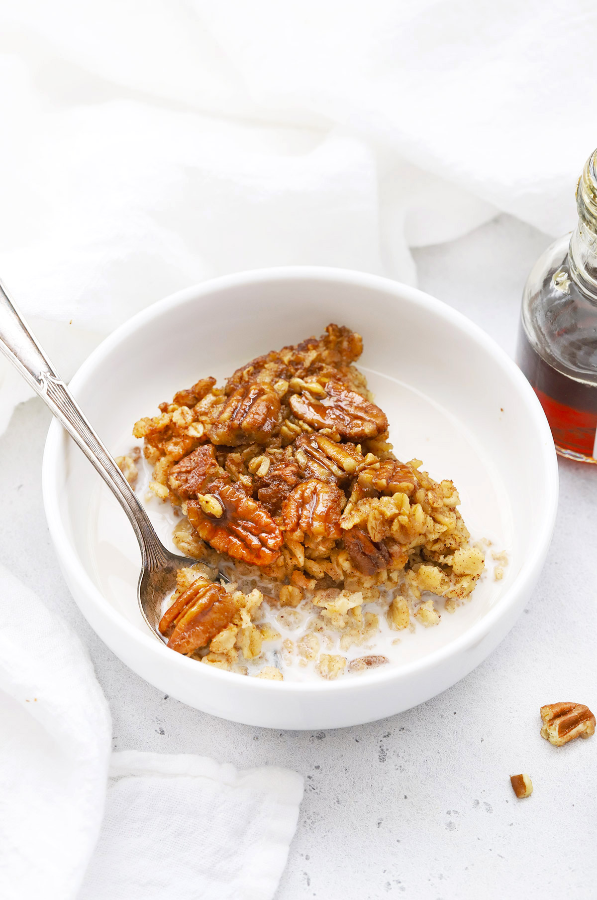 Warm bowl of pecan pie baked oatmeal drizzled with almond milk