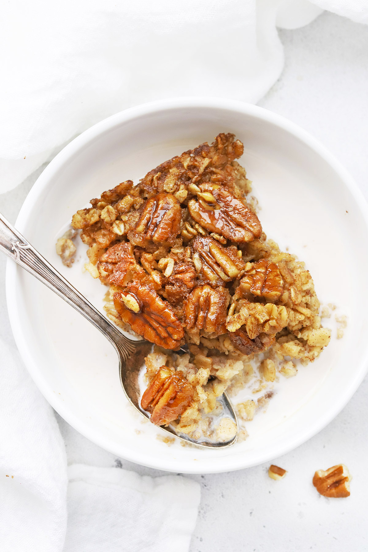 Overhead view of a warm bowl of gluten free pecan pie baked oatmeal with almond milk