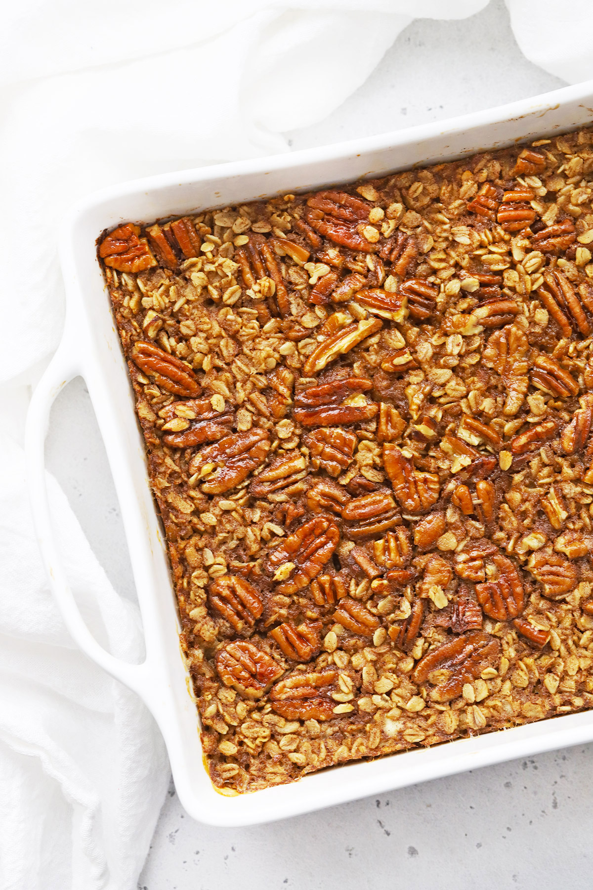 Overhead view of a square pan of gluten free + vegan pecan pie baked oatmeal