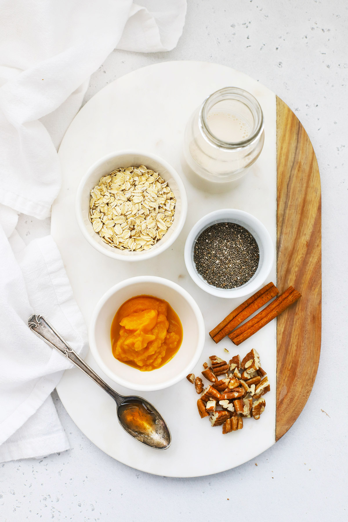 Ingredients for Pumpkin Overnight Oats set out on a marble board