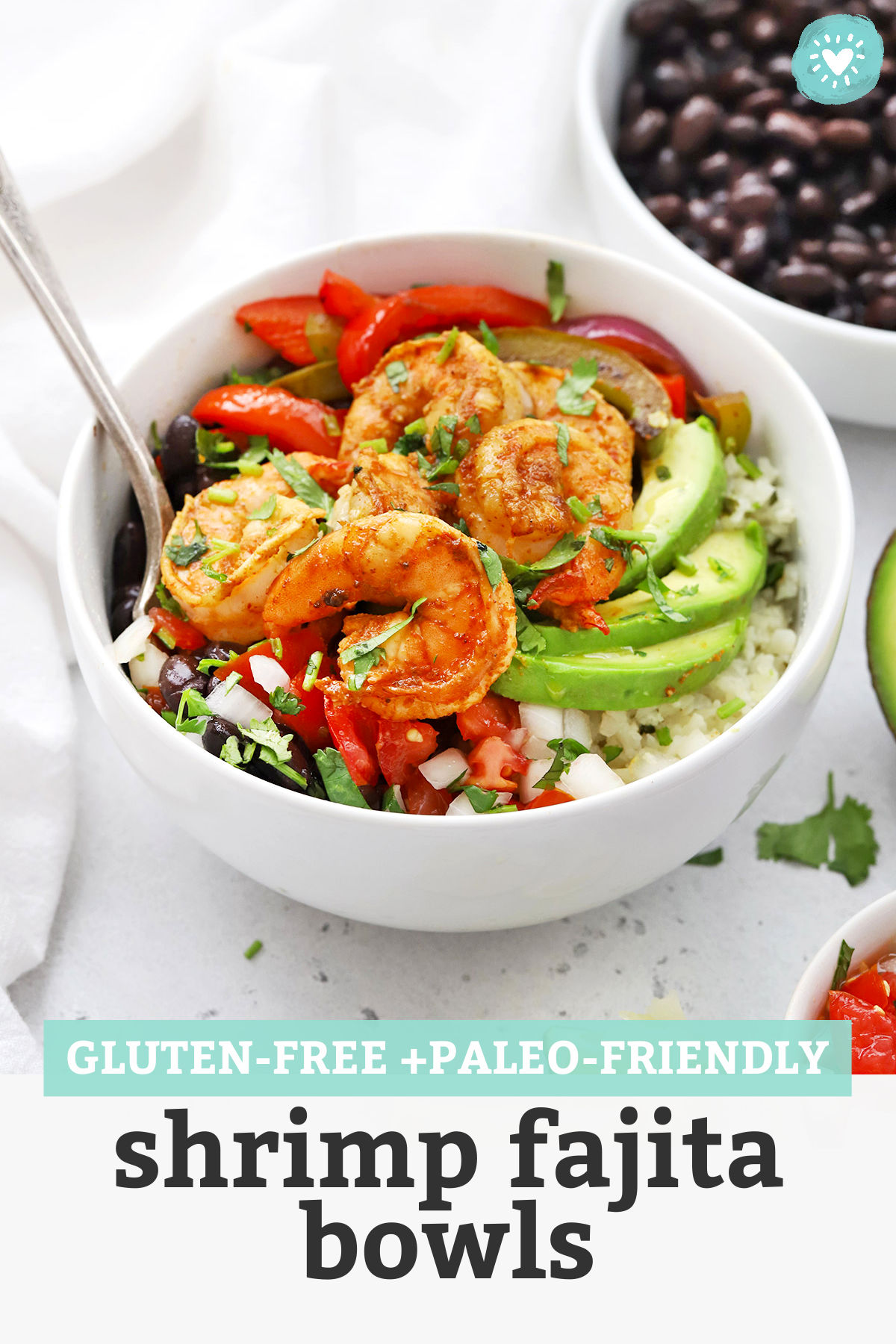 "Front view of Gluten Free Shrimp Fajita Bowls with avocado, black beans, and pico de gallo with text overlay that reads ""Gluten-Free + Paleo-Friendly Shrimp Fajita Bowls"""