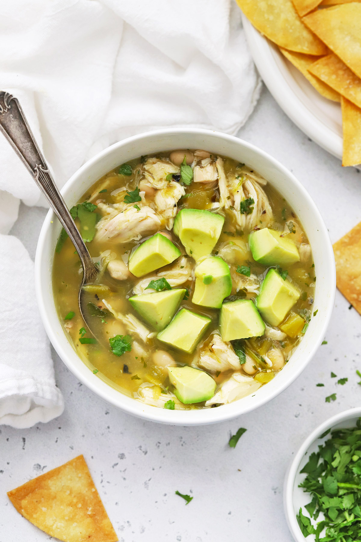 Salsa Verde Chicken Chili topped with diced avocado and minced cilantro