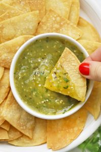 Close up view of a tortilla chip being dipped into homemade salsa verde (green salsa)