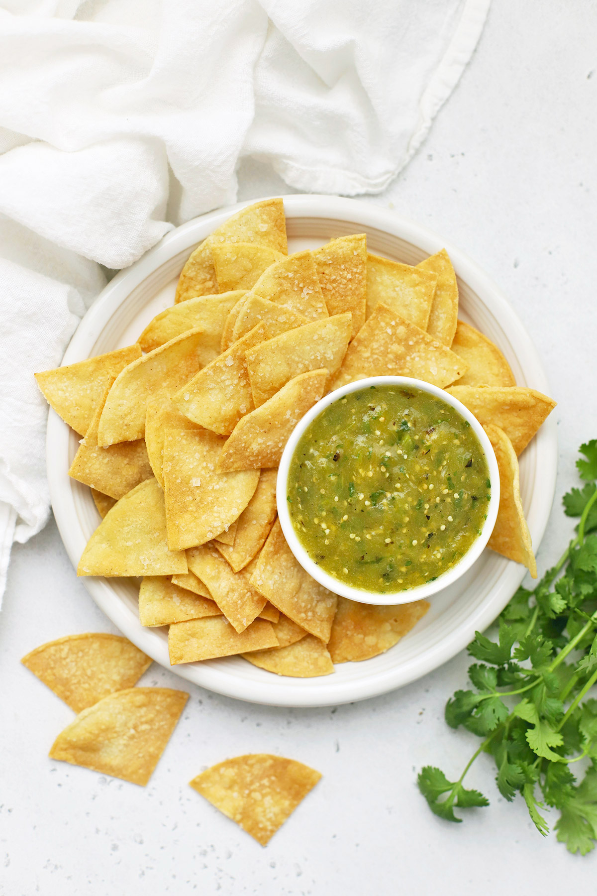 Overhead view of a plate of baked tortilla chips with a bowl of homemade salsa verde (green salsa)