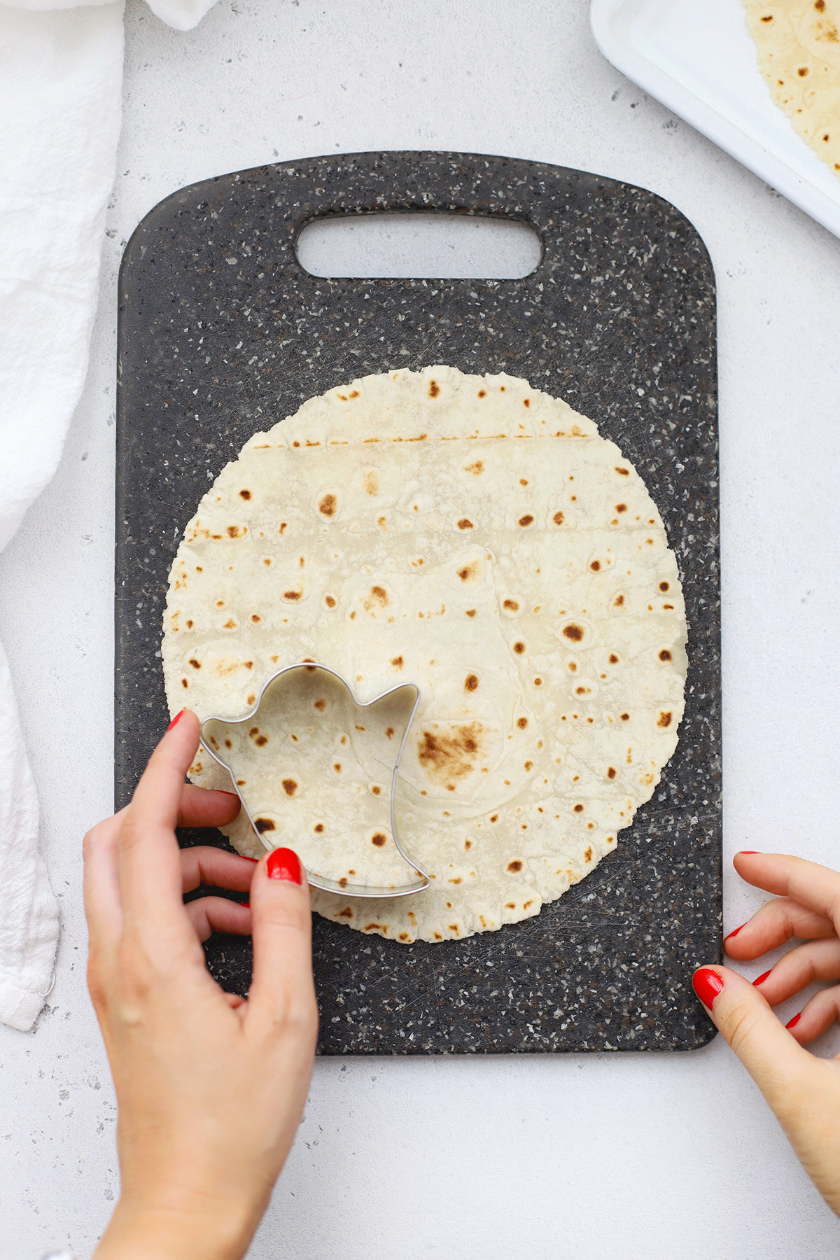 Using a ghost cookie cutter to cut out ghost chips from a gluten-free tortilla