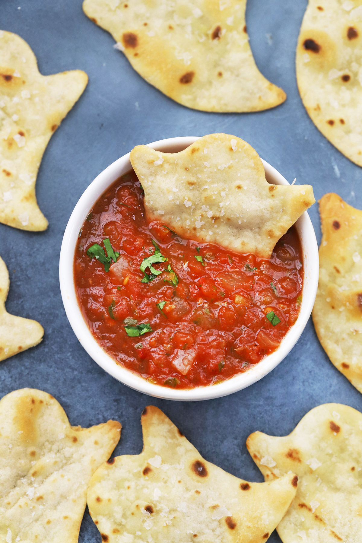 A close view of Baked Halloween Ghost Chips on a black background with a bowl of red salsa