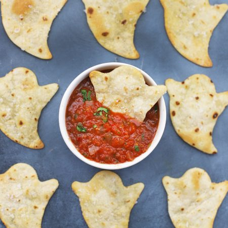 Baked Halloween Ghost Chips on a black background with a bowl of red salsa