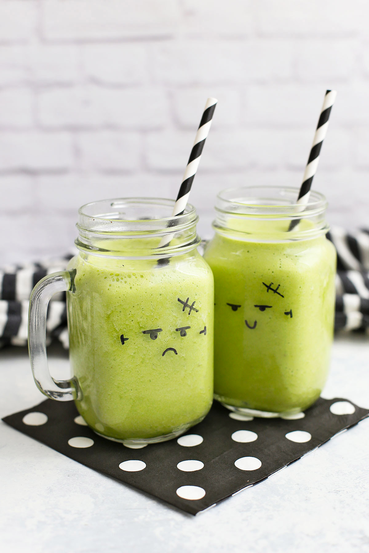Two green smoothies in glasses with monster faces drawn on them.