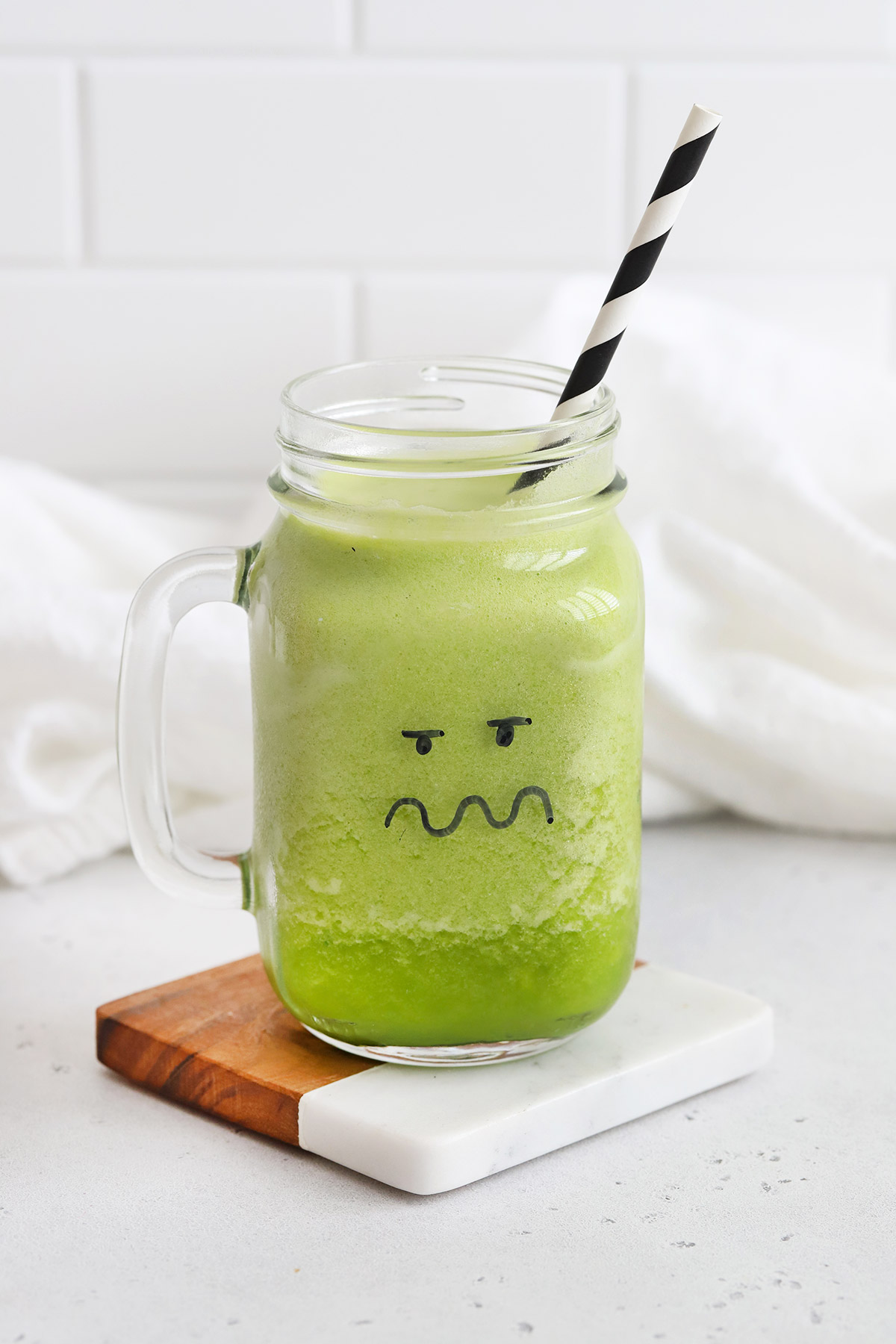 Green Monster Face Smoothie in a mason jar glass with a black and white striped straw