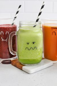 Purple, Green, and Orange Smoothies in glasses with monster faces drawn on them