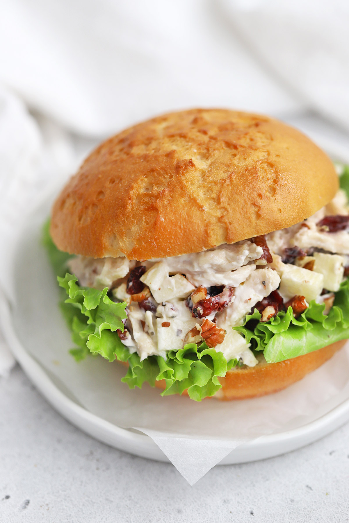 Close up view of an Apple Cranberry Chicken Salad Sandwich on a Gluten-Free Bun with Lettuce