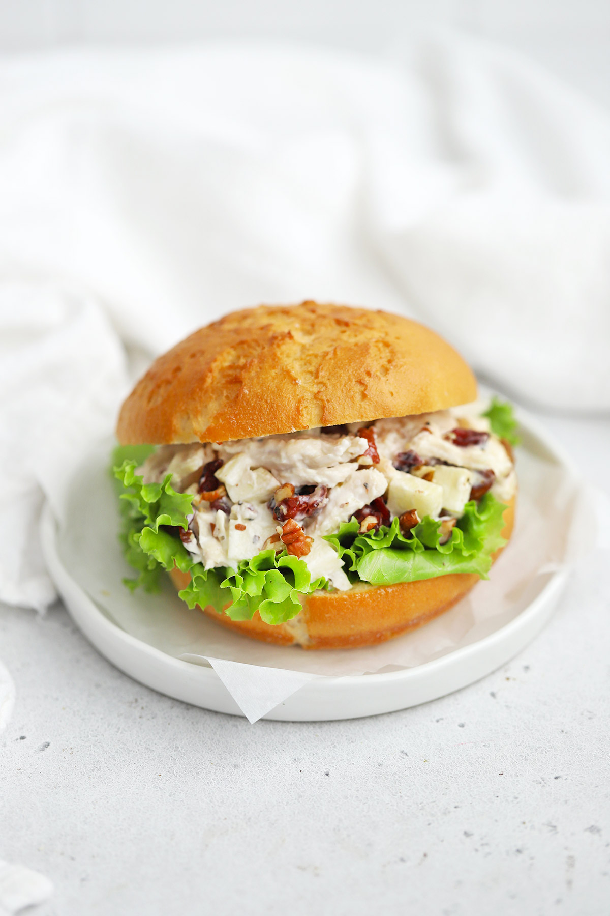 Front view of an apple cranberry chicken salad sandwich made with a gluten-free bun on a white plate.