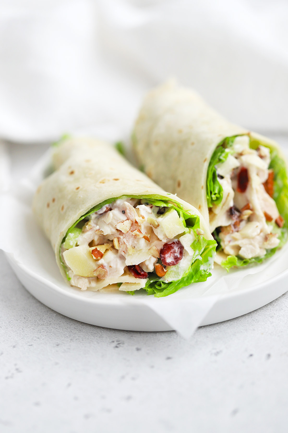 Close-up view of an Apple Cranberry Chicken Salad Wrap made with a gluten-free tortilla and lettuce.