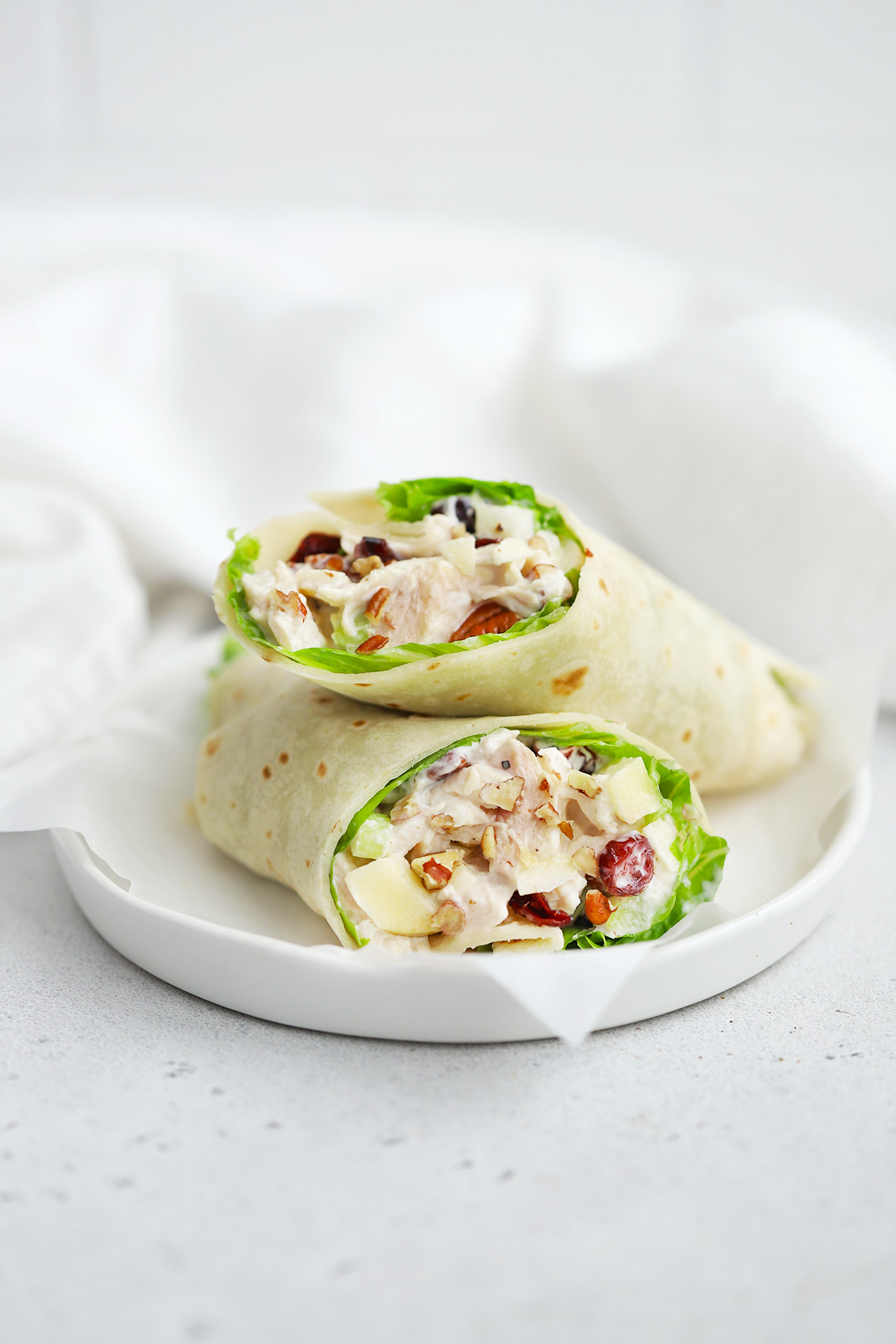 Front view of a halved apple cranberry chicken salad wrap made with a gluten-free tortilla