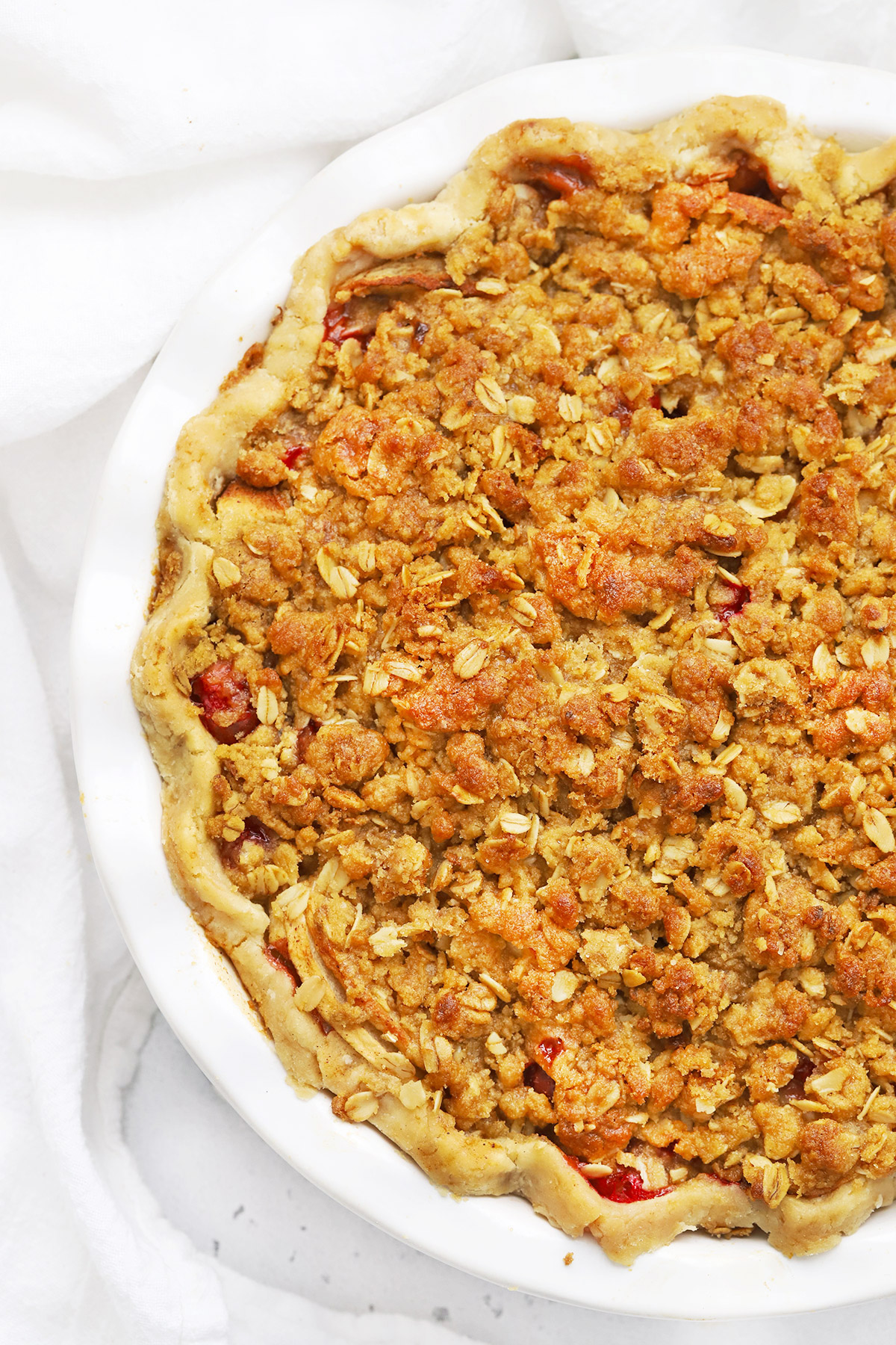 Close up view of an Apple Cranberry Crumble Pie on a white background