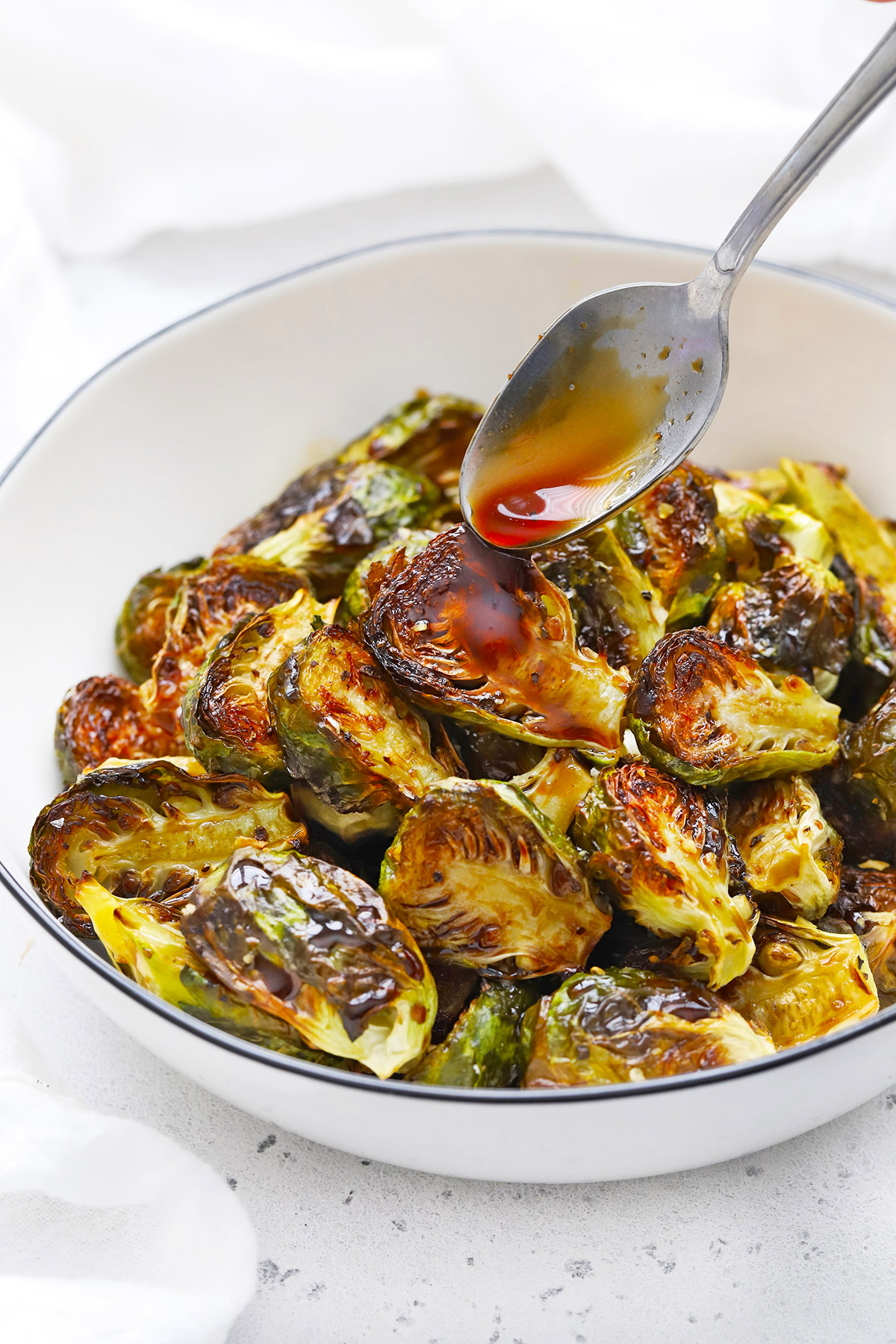 Drizzling balsamic glaze onto roasted Brussels sprouts