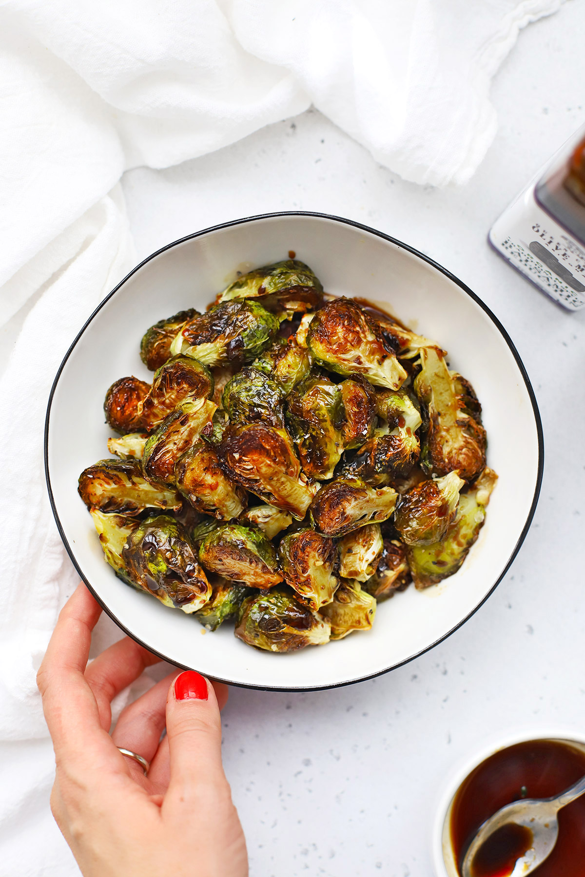 Setting down a bowl of Roasted Balsamic Brussels Sprouts on a white background