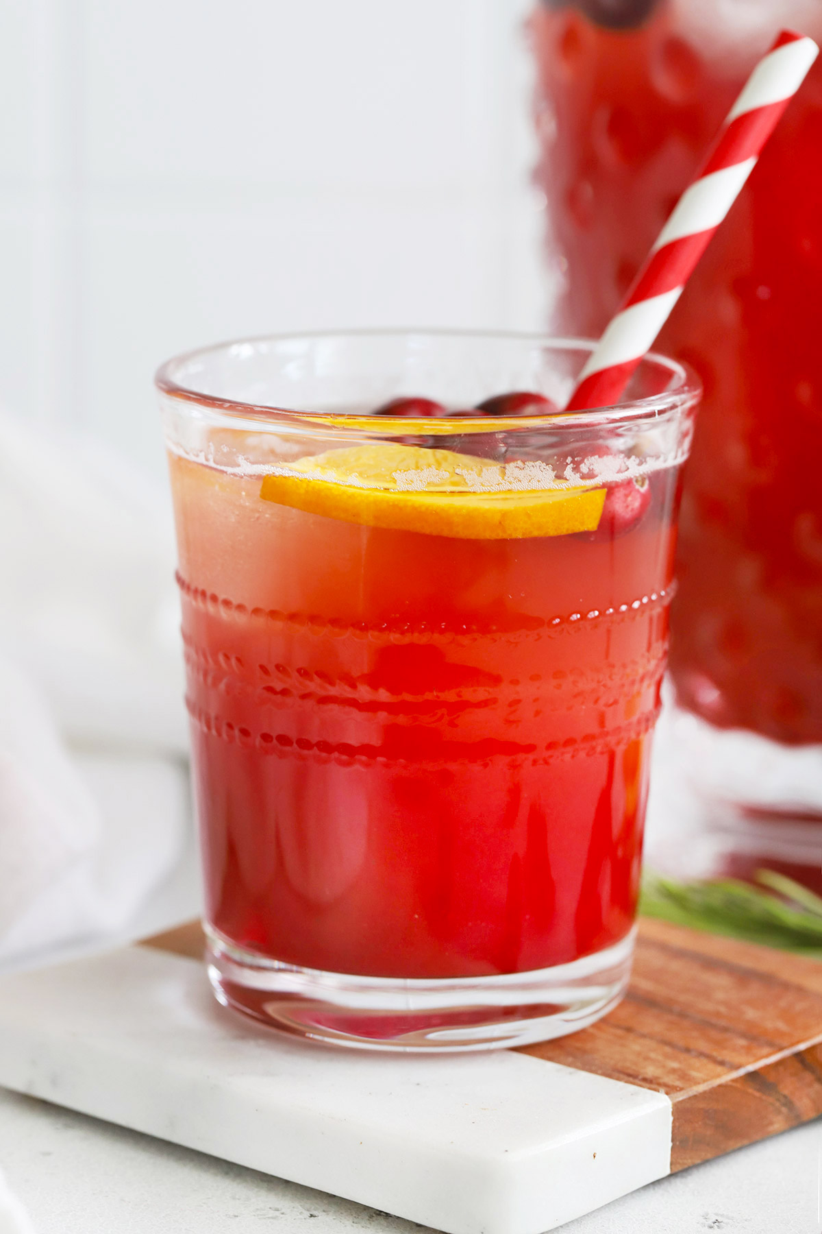 Close up Front view of a Cranberry Cider Mocktail on a marble and wood coaster on a white background