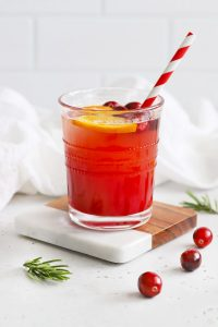 Front view of a Cranberry Cider Mocktail on a marble and wood coaster on a white background