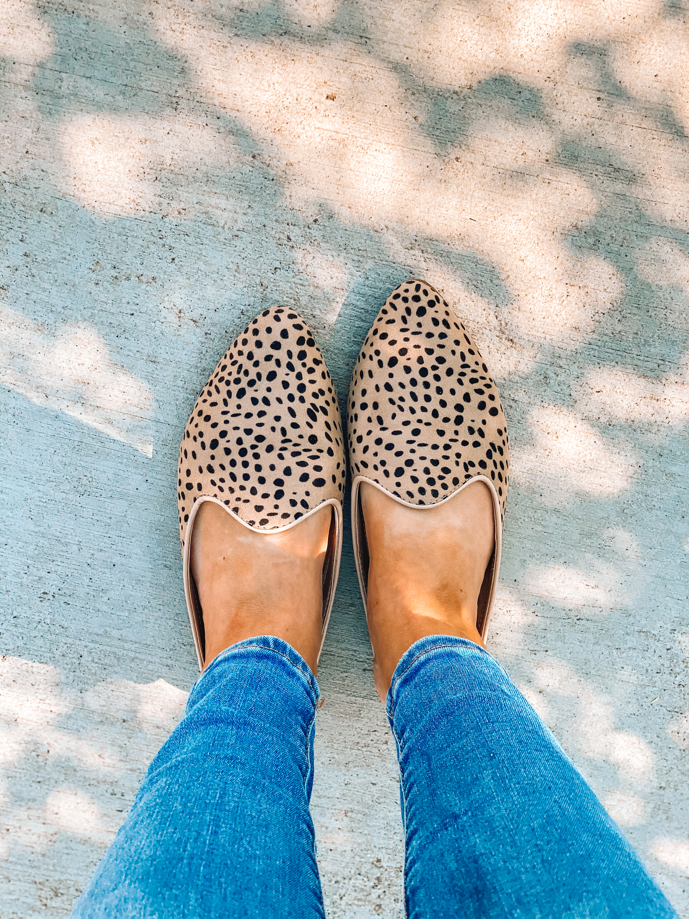 Overhead view of Emily from One Lovely Life's leopard mules from Target and jeans from American Eagle