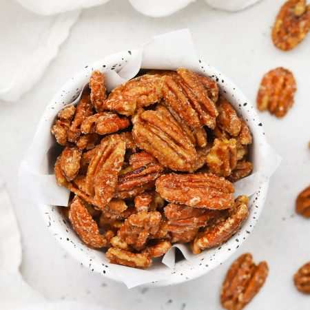 Overhead view of a speckled bowl of naturally sweetened maple candied pecans on a white background