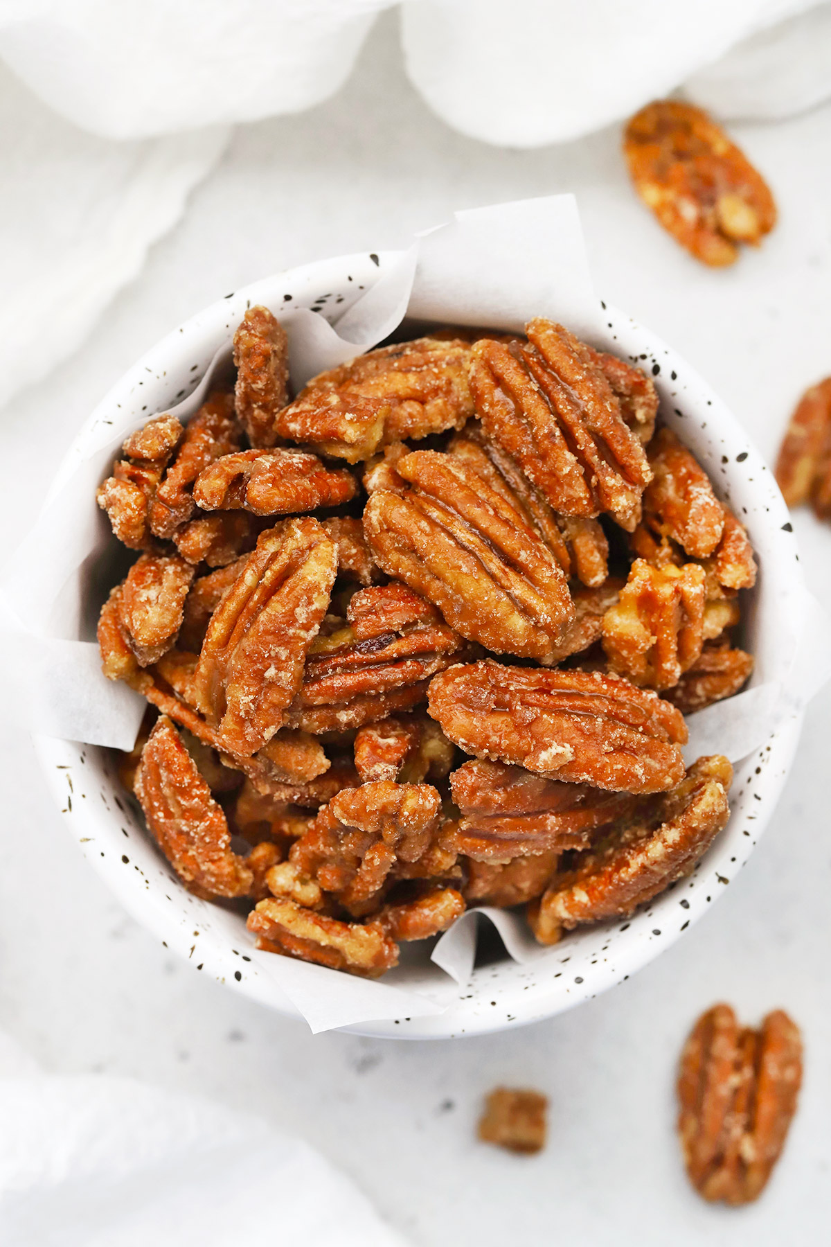 Close up overhead view of a speckled bowl of naturally sweetened maple candied pecans