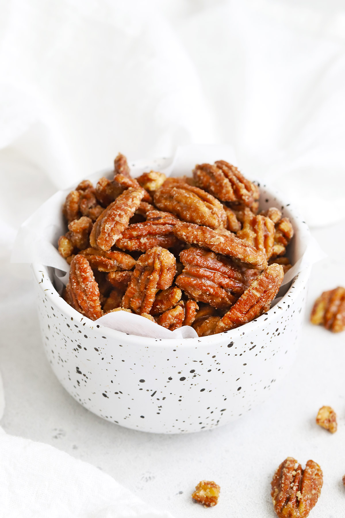 Front view of a speckled bowl of Naturally Sweetened Maple Candied Pecans