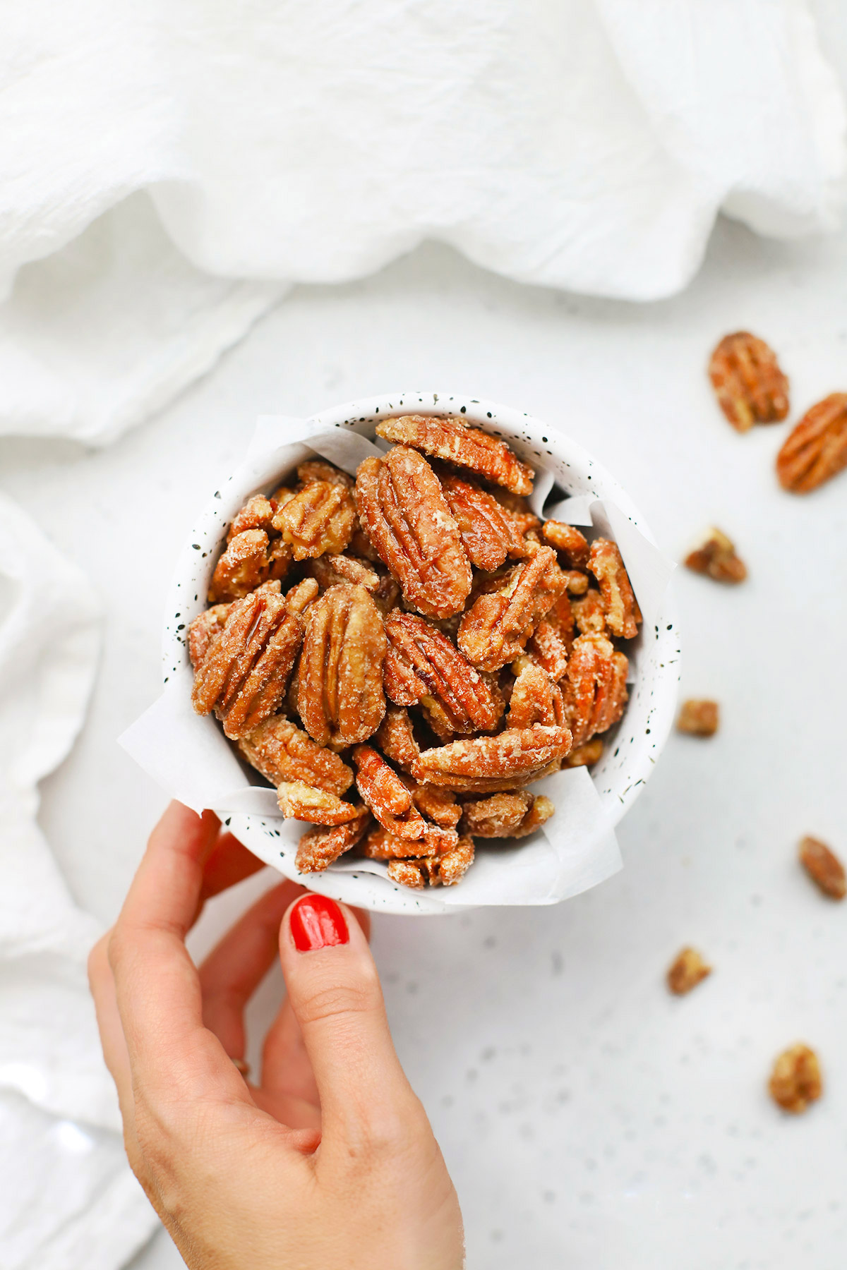 Hand setting down a speckled bowl of naturally sweetened maple candied pecans on a white background