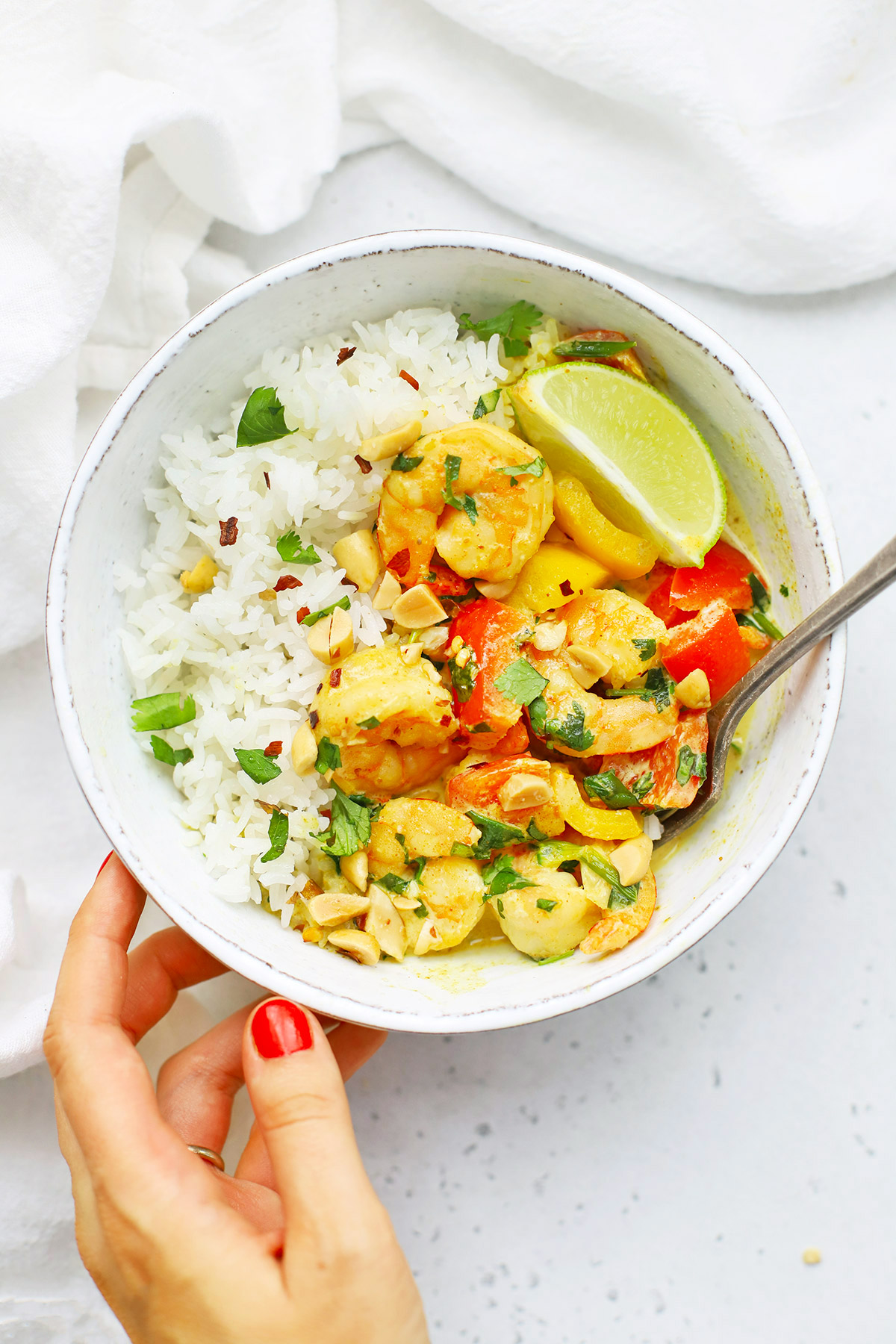 Setting down a bowl of coconut shrimp curry on a white background