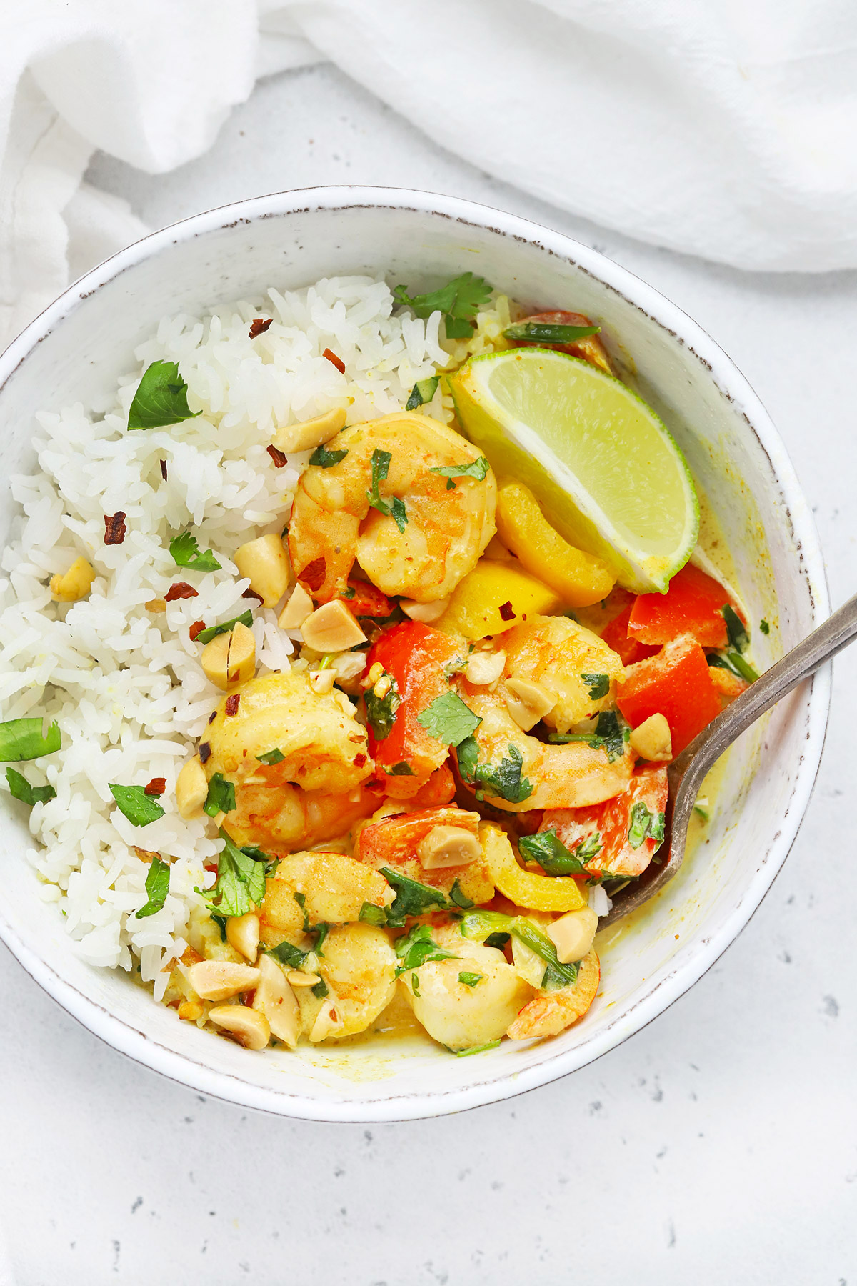 Overhead view of a bowl of paleo coconut shrimp curry with colorful veggies, crushed peanuts, and a fresh lime wedge