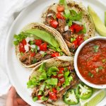 Overhead view of a plate of slow cooker barbacoa beef tacos with salsa and avocado