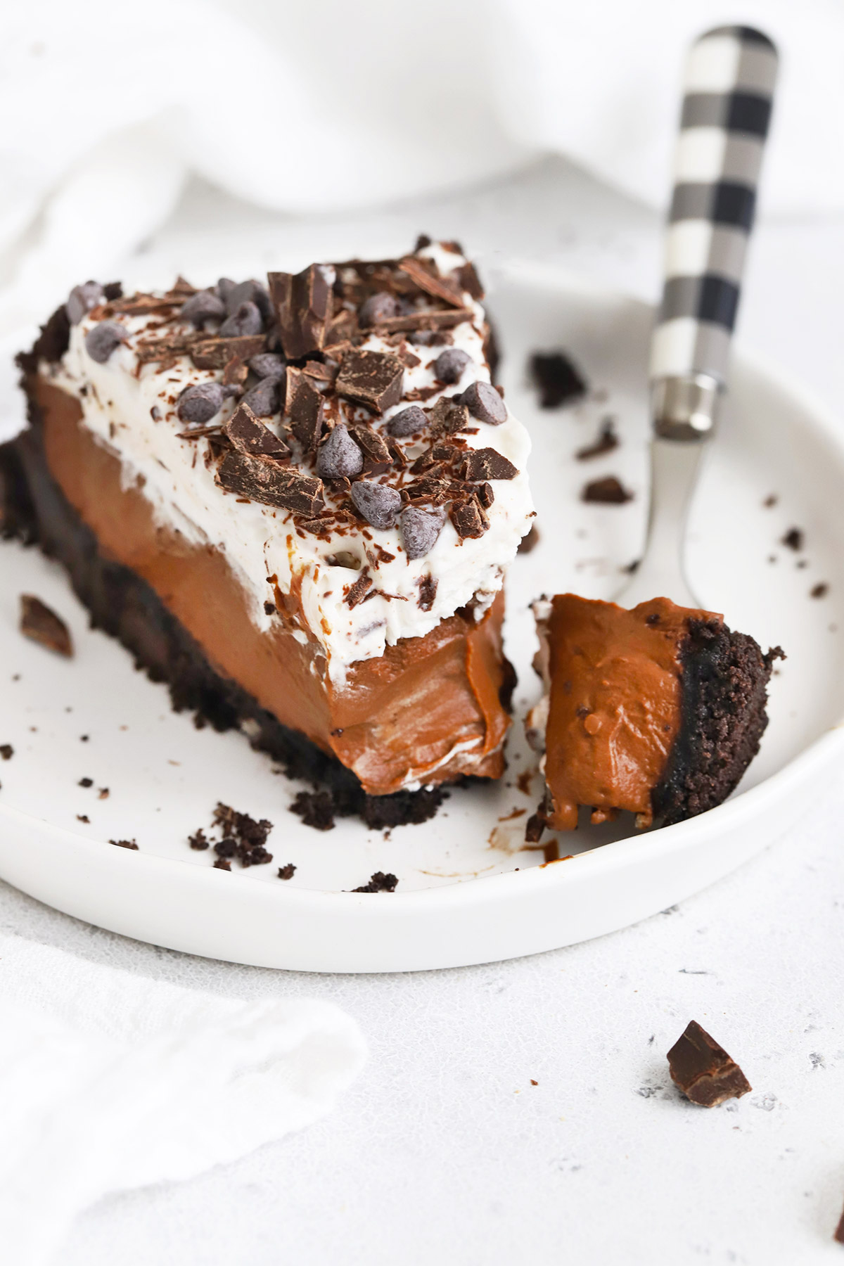 A slice of dairy-free vegan chocolate cream pie with chocolate cookie crust on a white plate with a white background