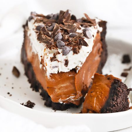 Front view of a slice of vegan chocolate cream pie with chocolate crust on a white plate with a white background