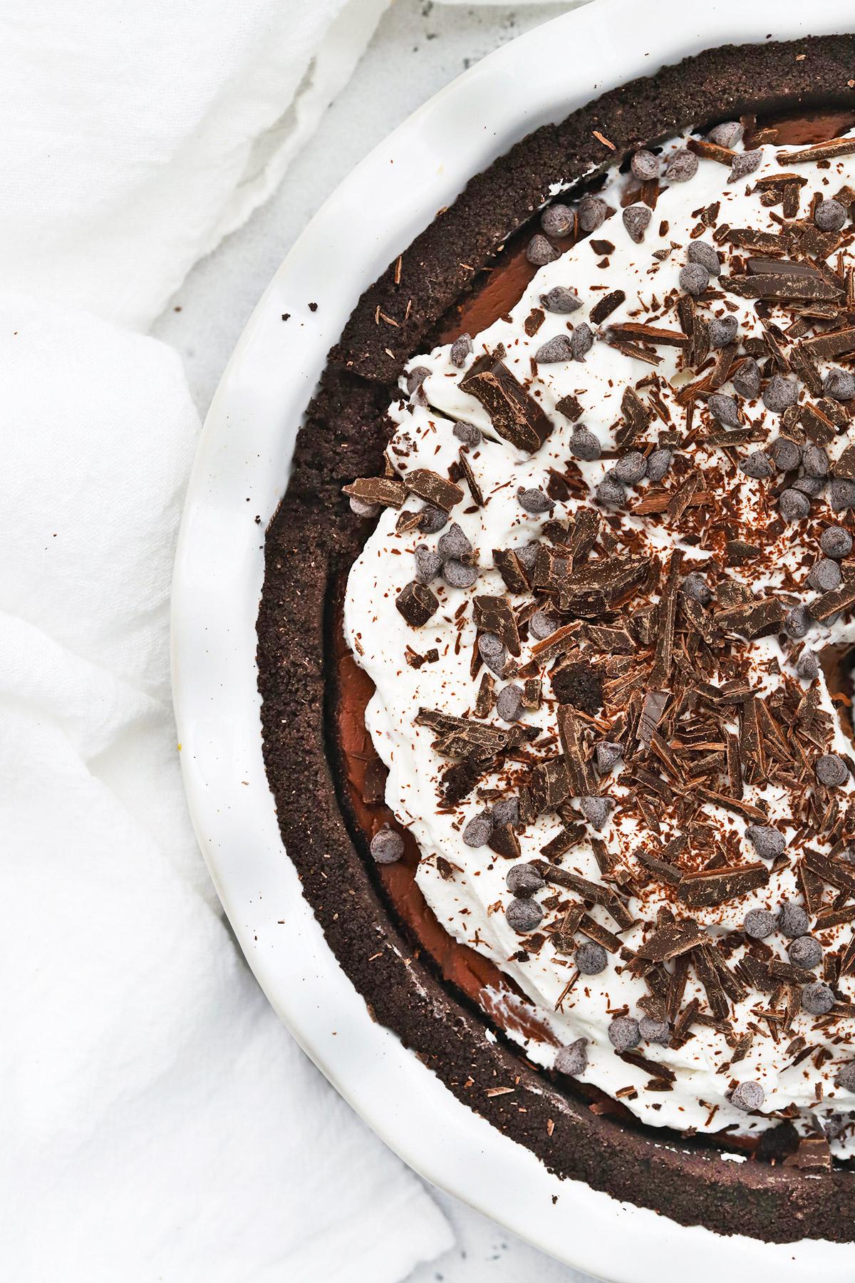 Close up overhead view of a dairy free vegan chocolate cream pie with chocolate cookie crust on a white background