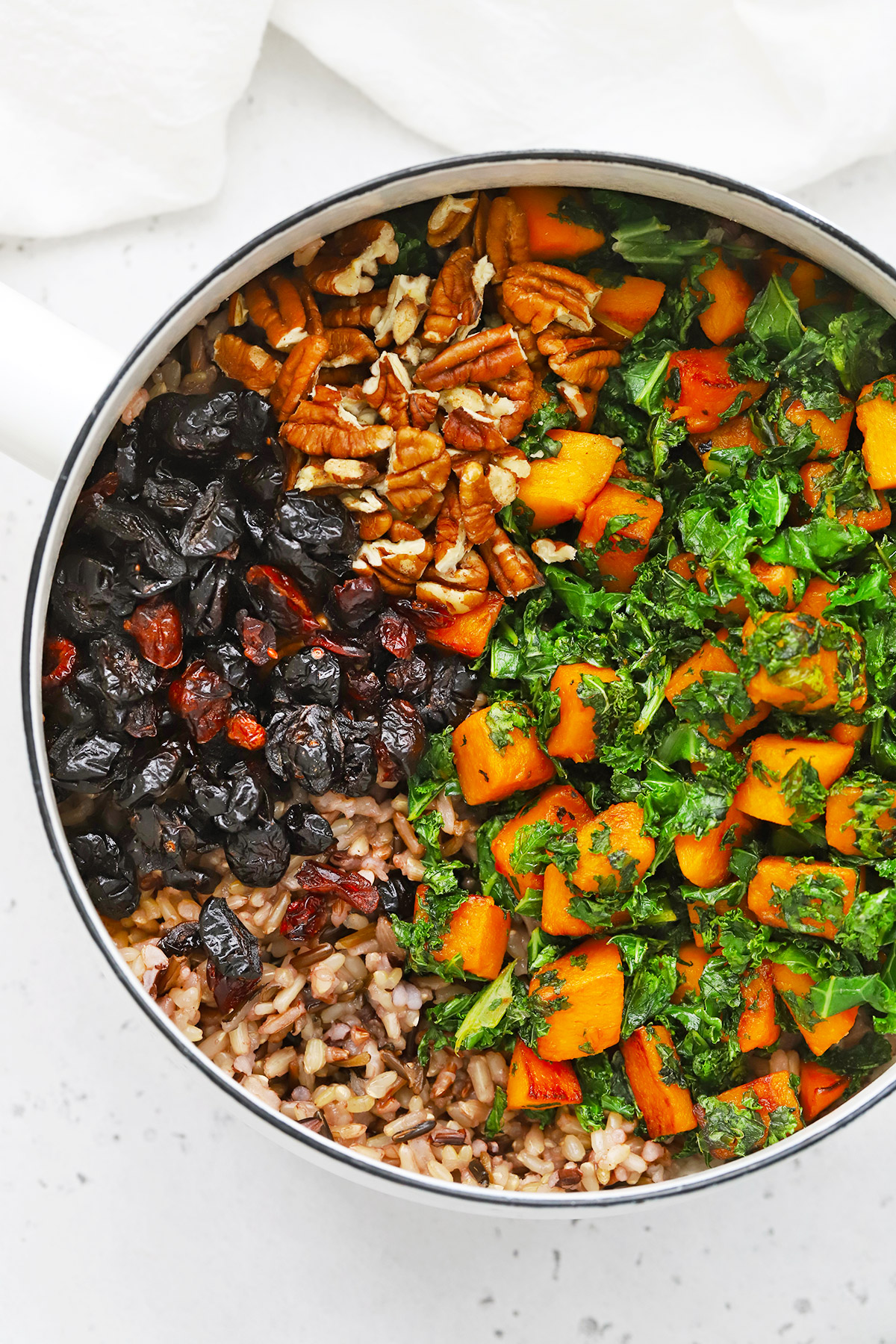 Overhead view of a saucepan with ingredienets for Wild Rice Pilaf ready to be mixed--wild rice blend, dried cranberries, toasted pecans, butternut squash, and kale
