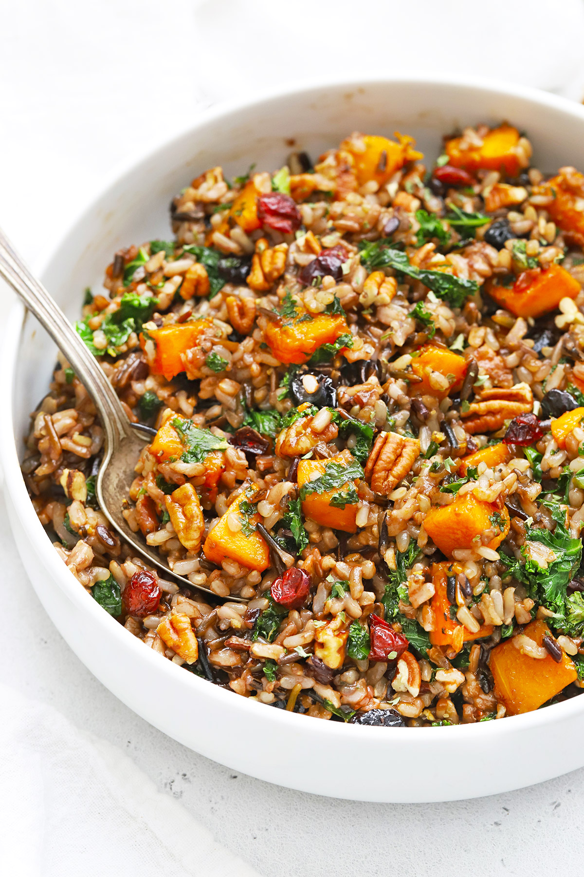 Front view of a white serving dish of Wild Rice Pilaf with Butternut Squash, Pecans, and Cranberries on a white background
