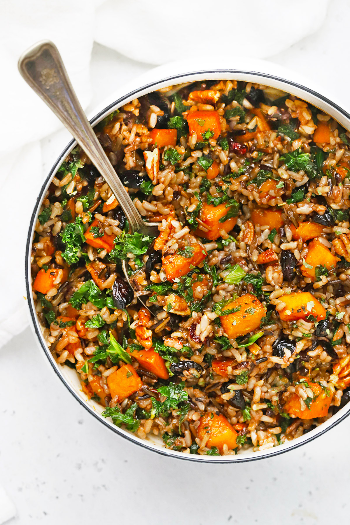 Overhead view of a saucepan of Wild Rice Pilaf with Butternut Squash, Kale, Dried Cranberries, and Pecans