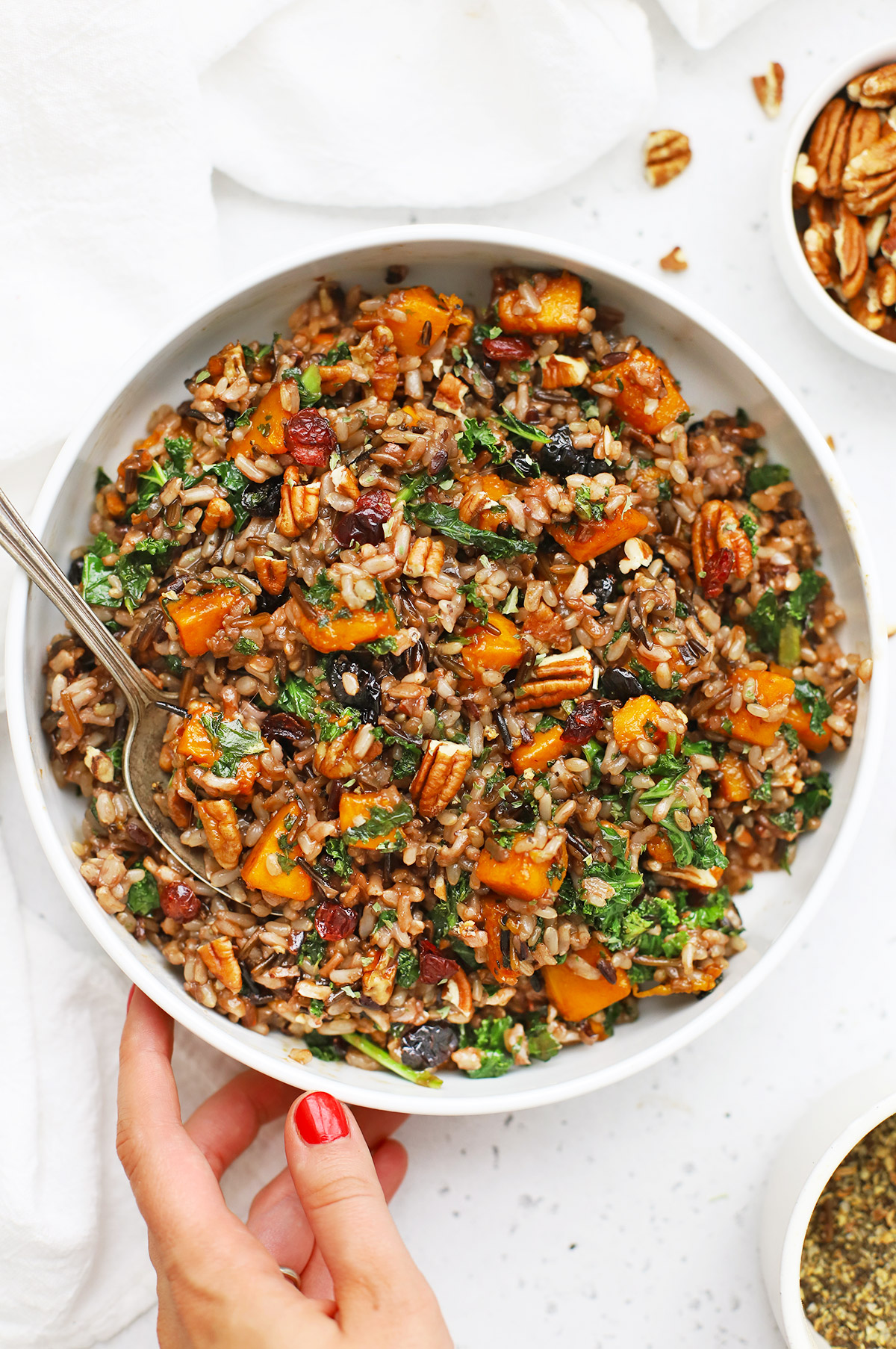 Overhead view of setting down a white bowl of Wild Rice Pilaf with Butternut Squash, Kale, Dried Cranberries, and Pecans