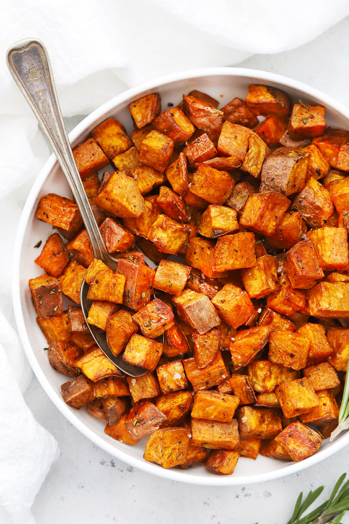 Overhead view of Cinnamon Rosemary Sweet Potatoes in a white bowl on a white background