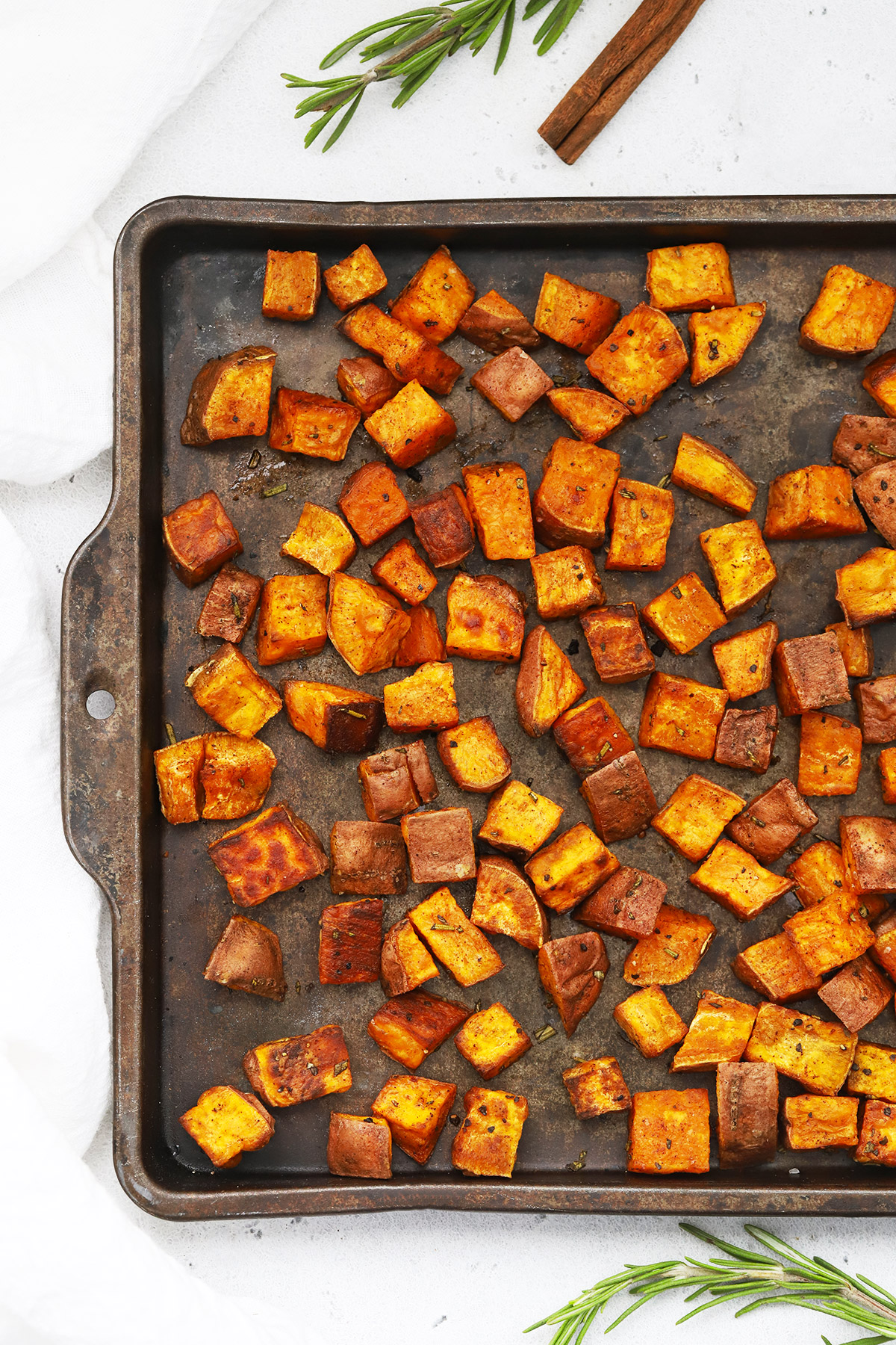 Overhead view of cinnamon roasted sweet potatoes on a baking sheet placed on a white background