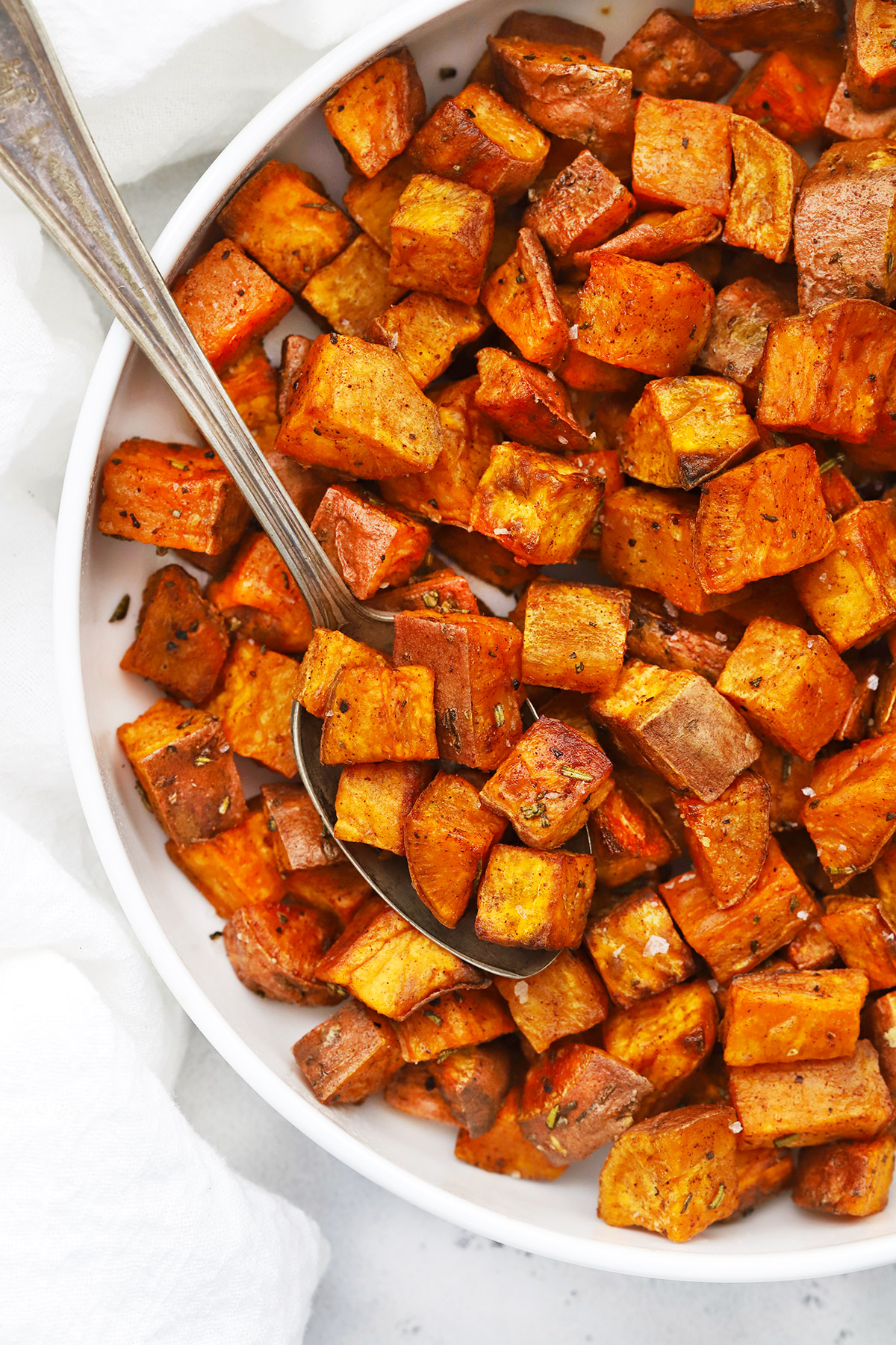 Close up Overhead view of Cinnamon Rosemary Sweet Potatoes in a white bowl on a white background