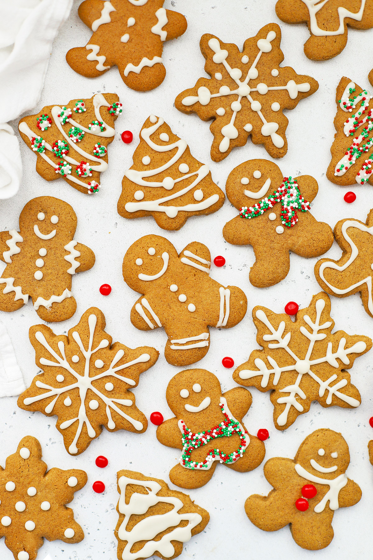 Overhead view of decorated gluten-free gingerbread cookies shaped like gingerbread men, snowflakes, and trees on a white background