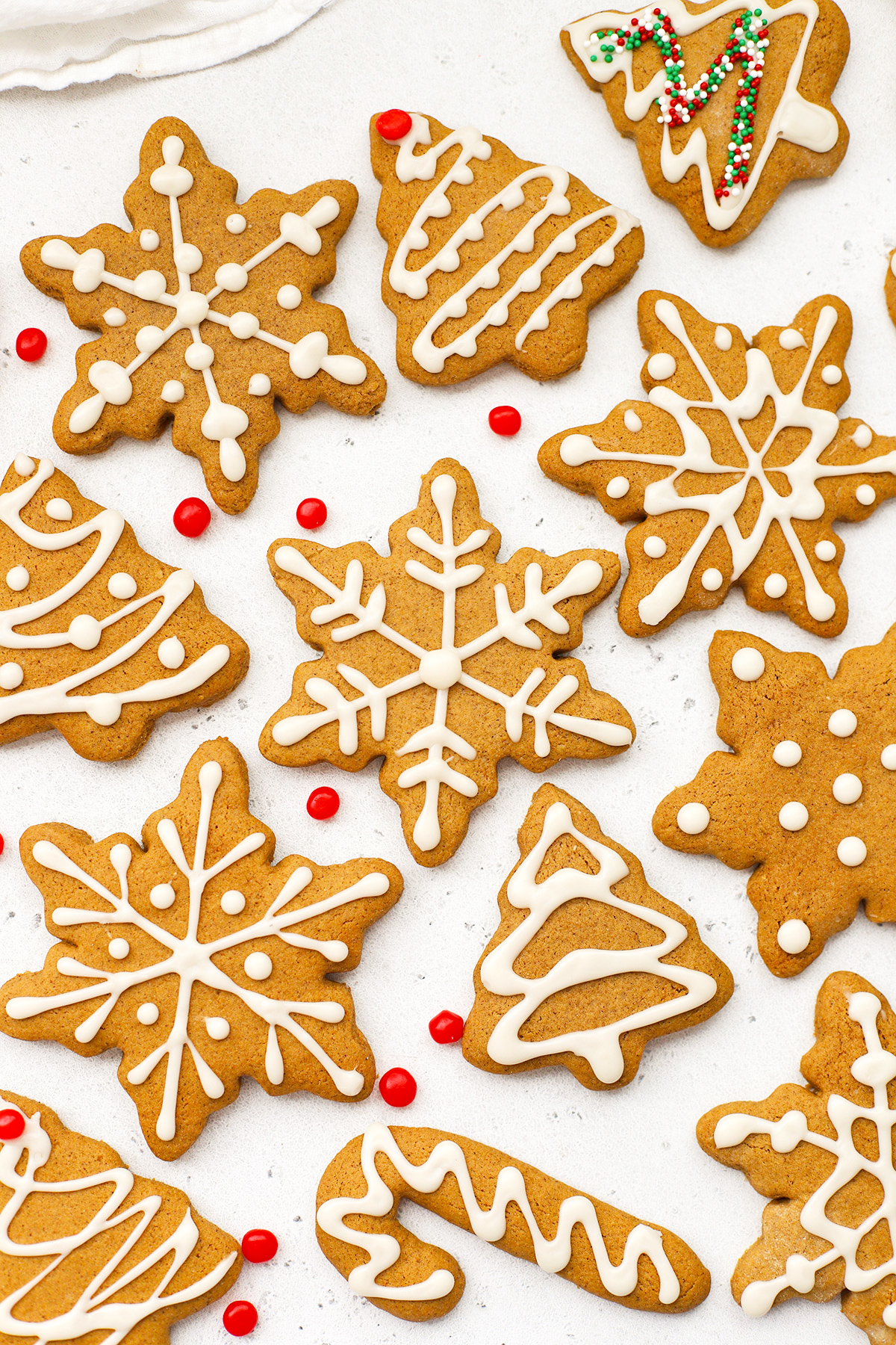 Overhead view of decorated gluten-free gingerbread cookies with white icing on a white background