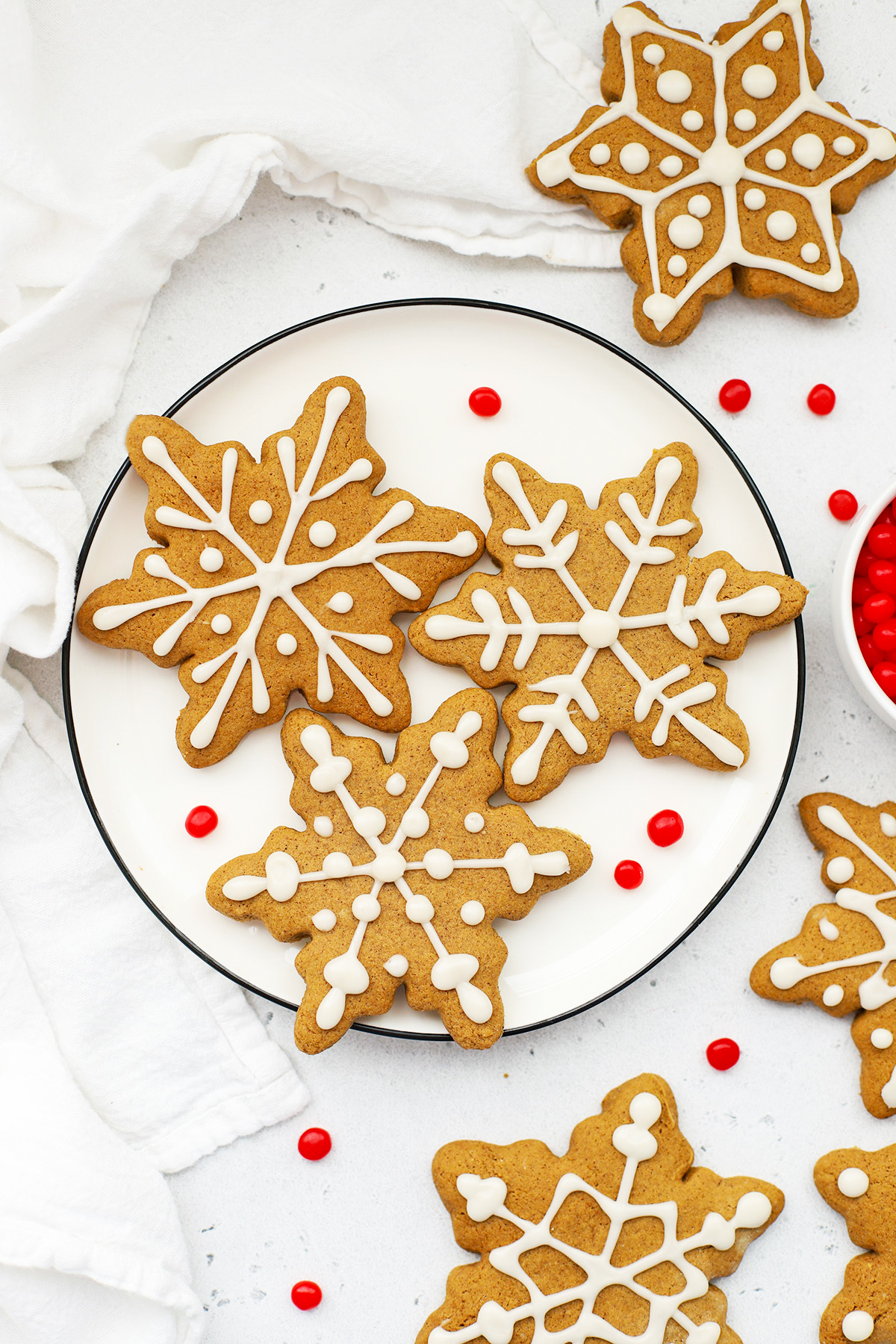 Overhead view of a plate of gluten-free gingerbread cookies decorated like snowflakes on a white background