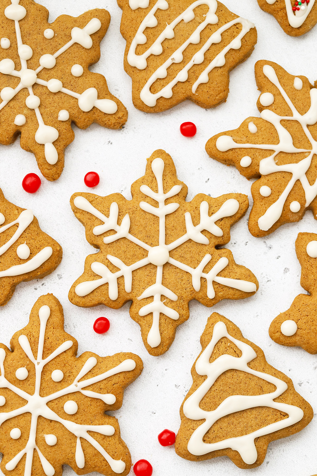 Close up Overhead view of decorated gluten-free gingerbread cookies with white icing on a white background