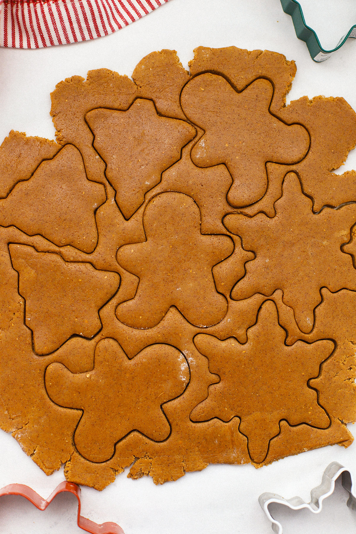 Close up view of gluten-free gingerbread cookie dough with cutout shapes on a white background