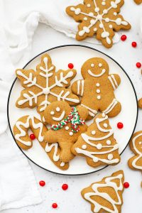 Overhead view of a plate of decorated gluten-free gingerbread cookies on a white background with red hot candies scattered around