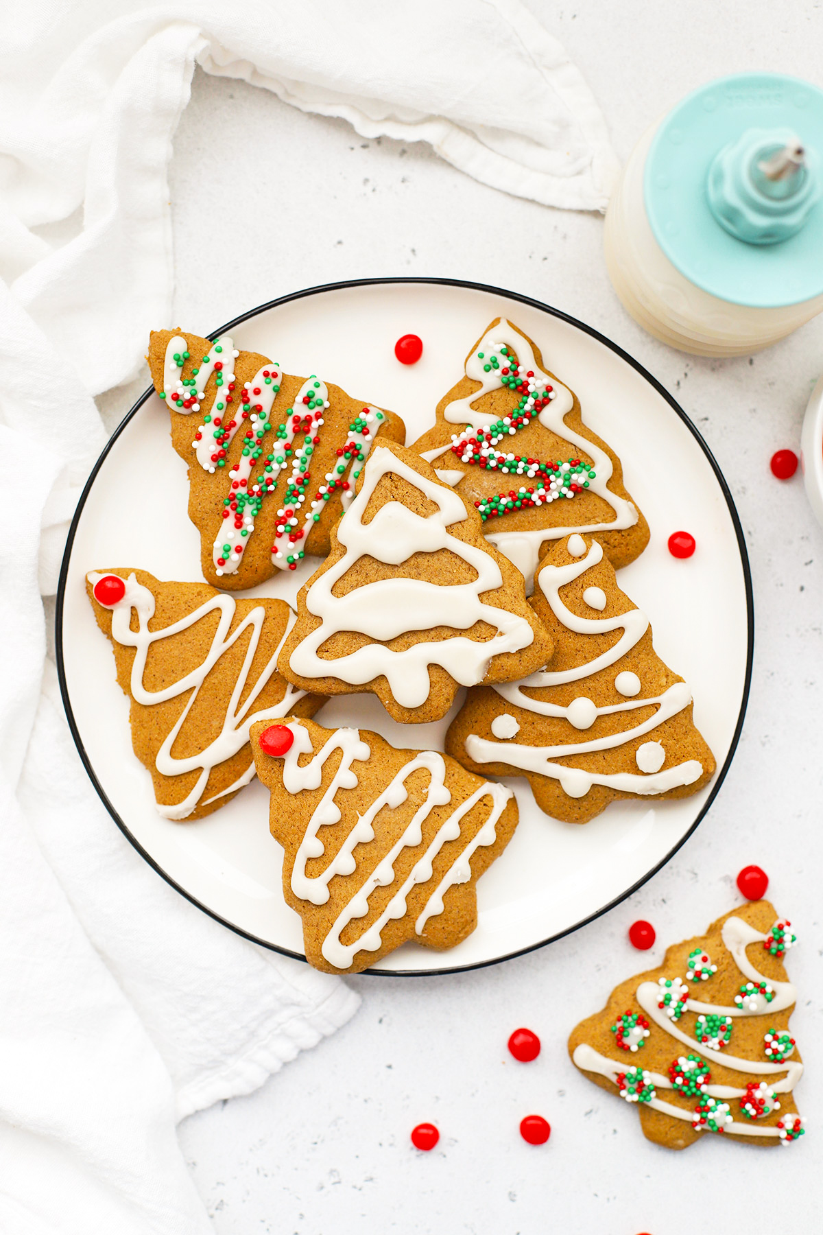 Overhead view of a plate of gluten-free gingerbread cookies shaped like trees decorated with white icing on a white background